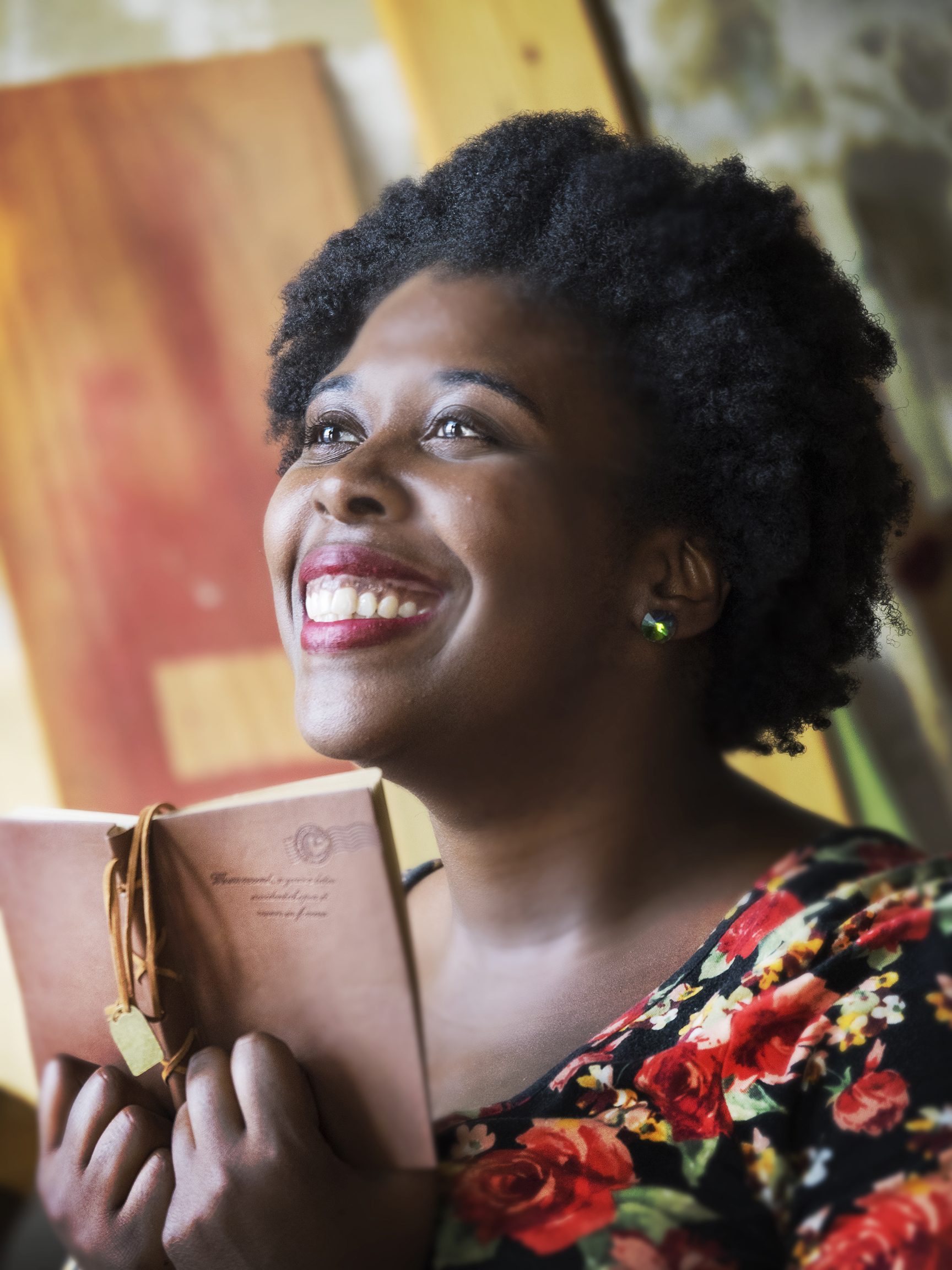 Noelle Brooks, marketing storyteller, is smiling upwards while holding a brown leather journal in front of her.
