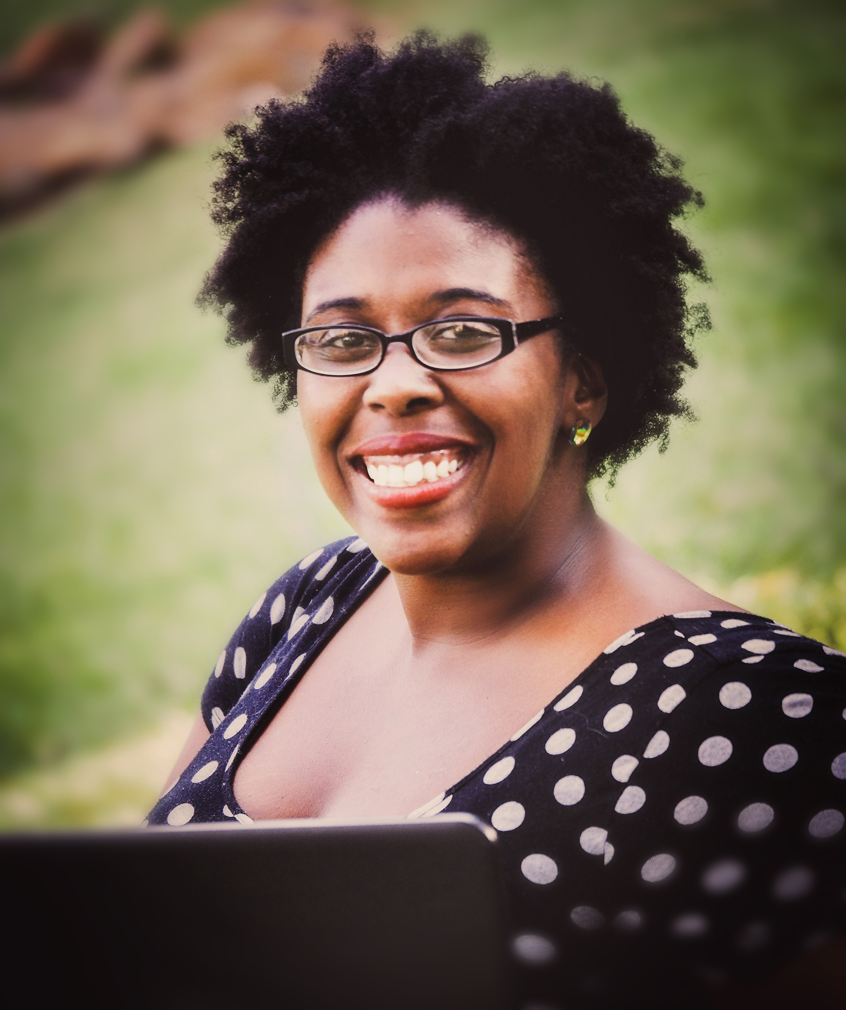 Noelle Brooks, marketing storytelelr, is smiling at the camera in front of a laptop.