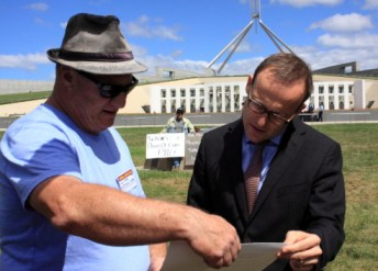 Loz Lowrey shows Adam Bandt the Peoples Vote of No Confidence in the Abbott Government.(Photo: Wayne Jannson).