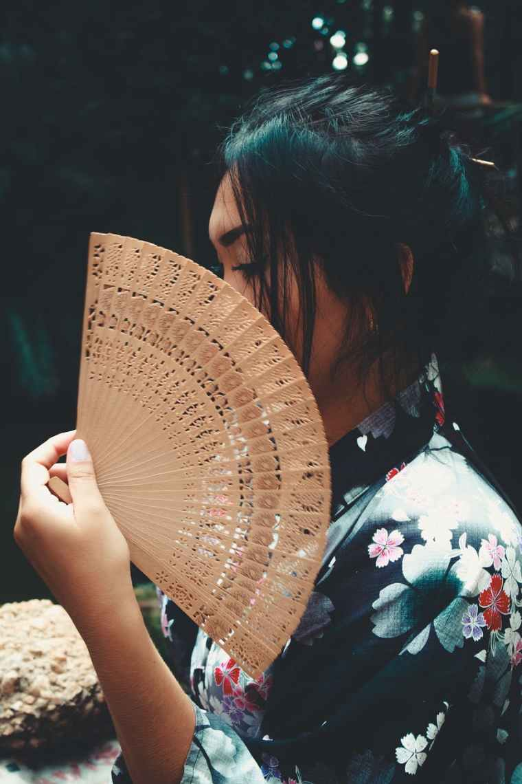 japanese woman holding brown hand fan