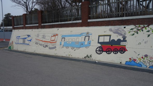 painting of trains on a wall outside museum in style of a childs drawing