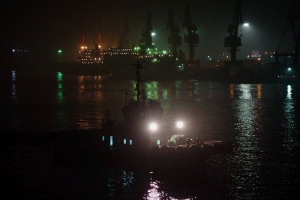 harbour in darkness, tug boat in foreground, cranes in background
