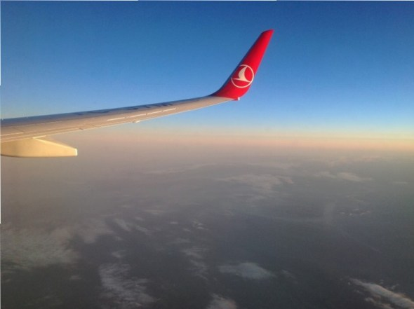 Turkish airlines wing, view of land below and rising dawn