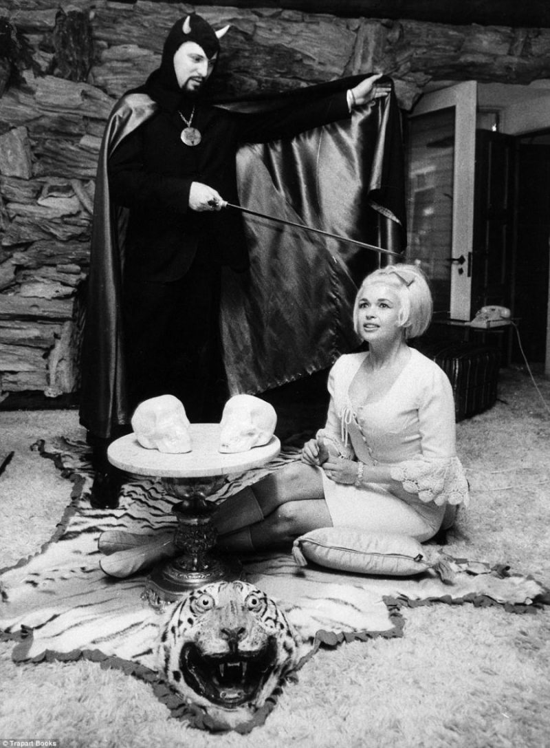 Mansfield 66/67. Anton LaVey stands over Jayne Mansfield with a sword. He wears a horned skullcap, she a virginal white dress.