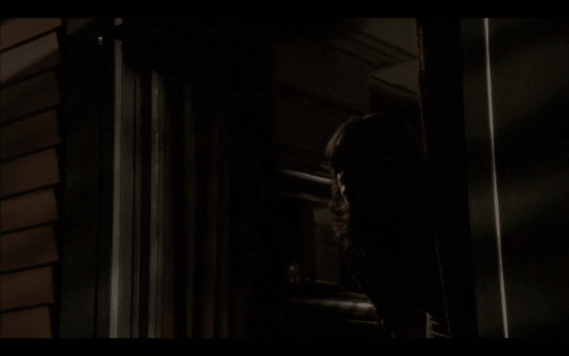 A girl looking out the window of a house into the darkness.