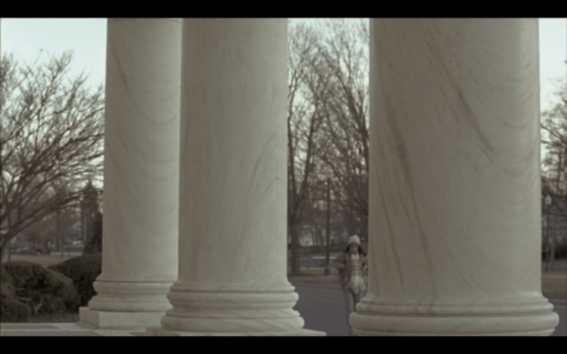 A girl between tall white pillars. The House of the Devil.