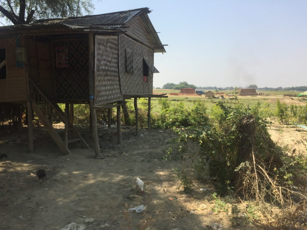 Bamboo and wood home on stilts beside the dry bed of the Irrawaddy River
