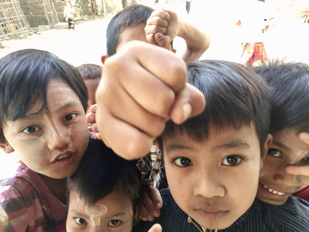 Close up photo of six young children smiling and mugging for the camera