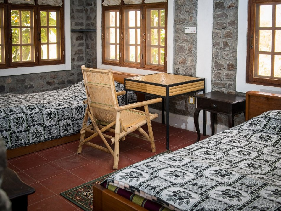 Interior of bedroom at Lei Thar Gone Guesthouse. Two single beds, desk with chair and several windows.