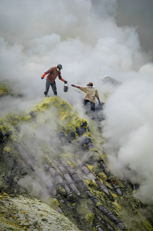 Miners carrying mined sulphur amidst the fumes at Kawah Ijen