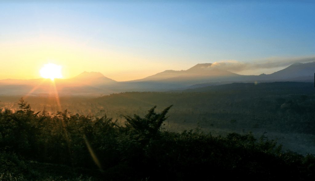 Sunrise over the mountains and a blue sky near Kawah Ijen
