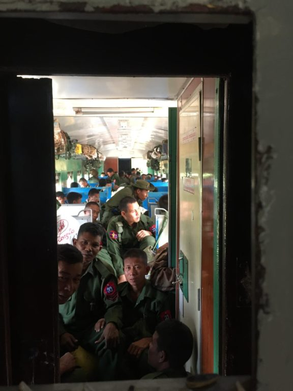 Looking through the window at Burmese military that fill the adjacent train carriage