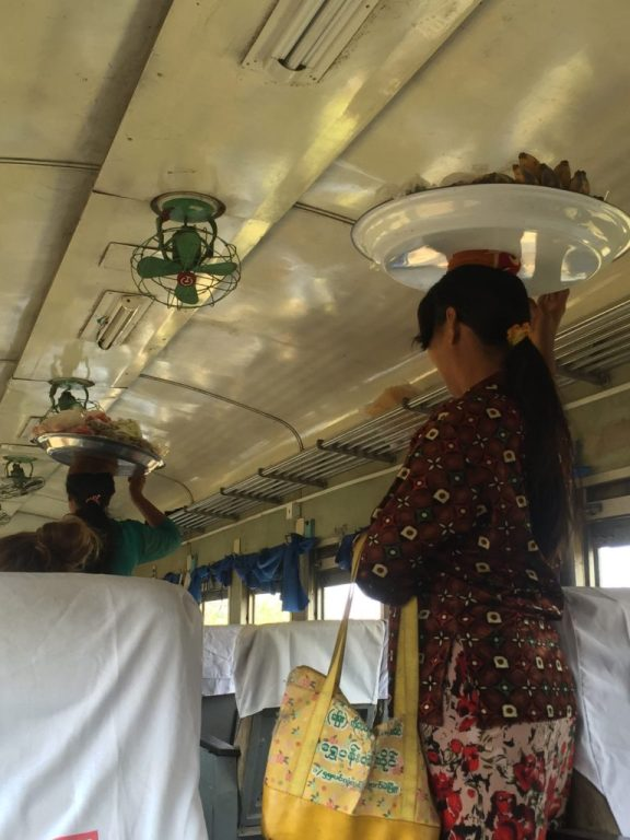 Vendors walk the train aisle balancing food on trays atop their heads