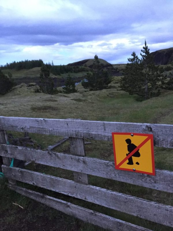 No pooping sign tacked on a fence with rolling hills and purple sky in the background