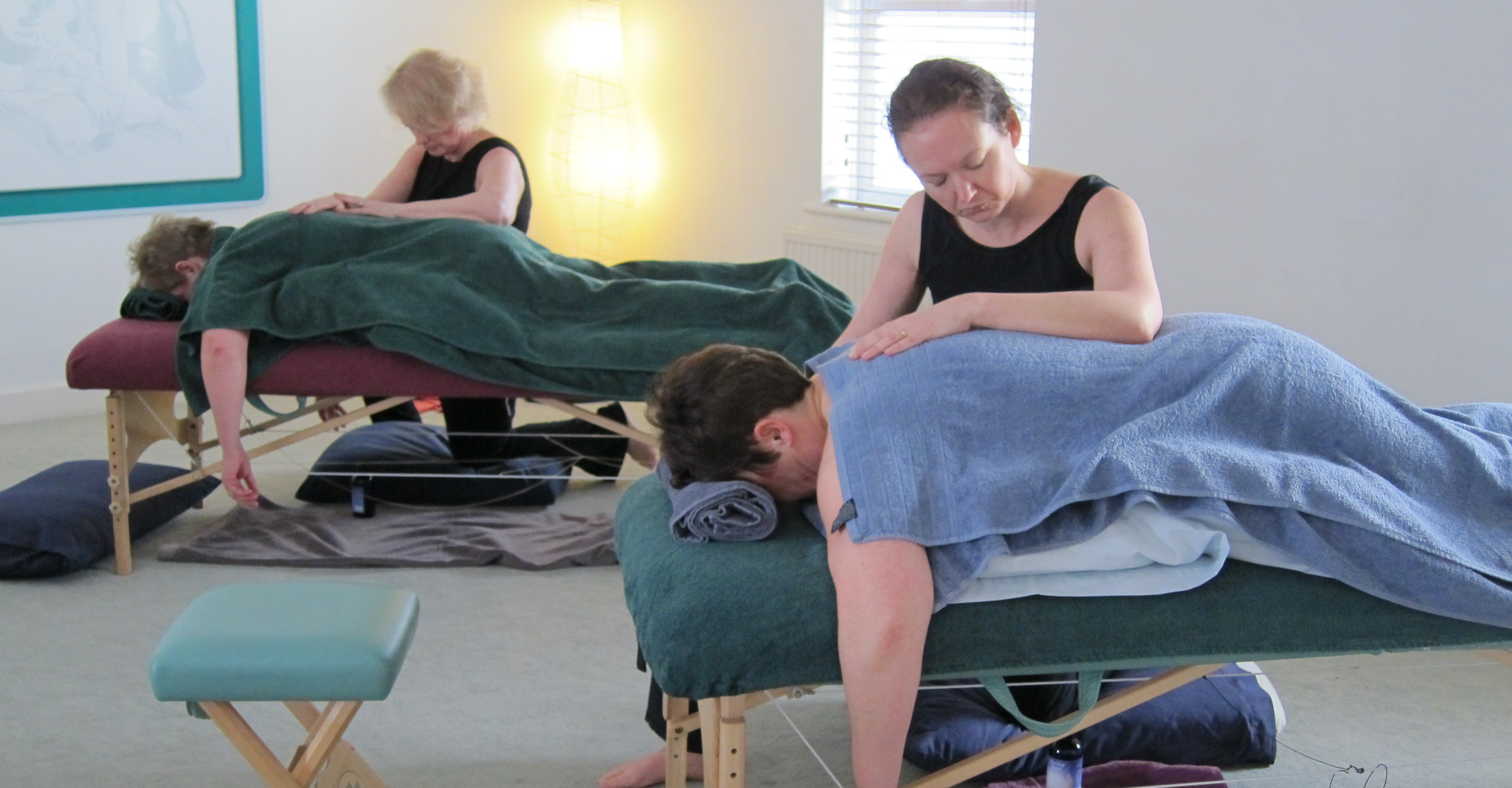Two massage practitioners giving gentle soothing touch