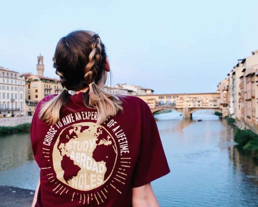 Girl wearing an IP t-shirt looking over the river in Florence.