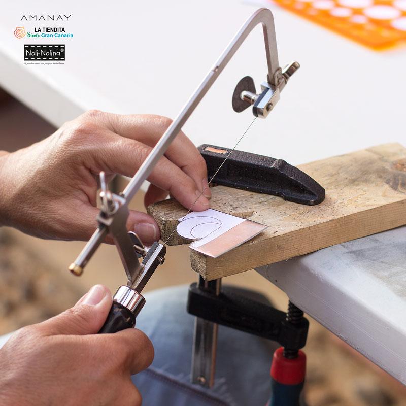 Manos cortando joya de metal con una sierra