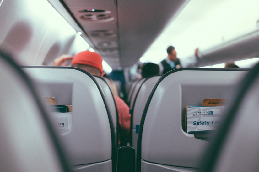 This is a picture of passengers in an airplane watching a flight attendant go over safety procedures for an airplane oxygen mask. This is an analogy for staying connected to God.