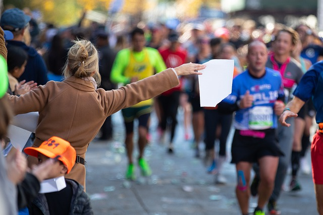 This is a picture of a woman holding a white towel toward a group of marathon runners to symbolize distraction from the Christian race.