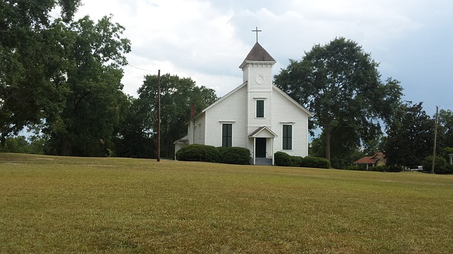Picture of a small white church in a field of green to represent the time I let God choose a church for me.
