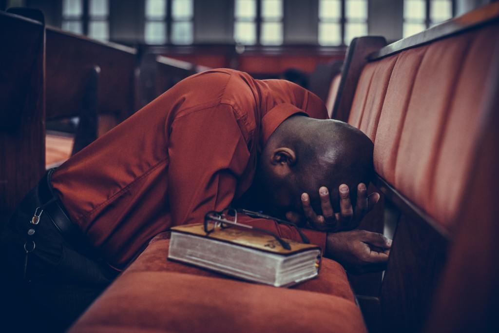 A man is praying at a church pew while holding his head in grief or stress. He needs a prayer that can change everything.