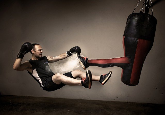 This is a picture of a man in boxing gloves being kicked by a leg coming out of a punching bag to represent victories and defeats.