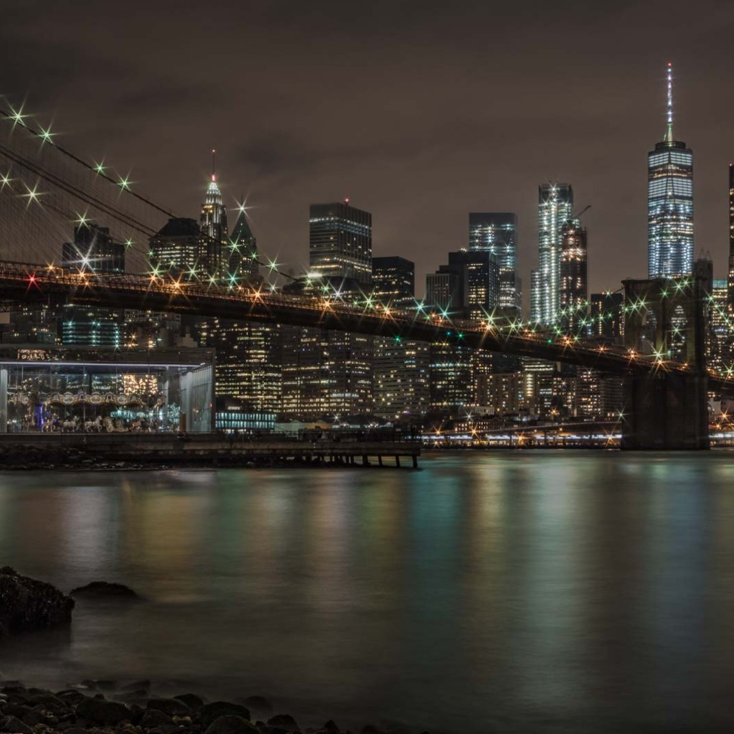 A night Picture of New York City Financial District Skyline and the Brooklyn Bridge. Photo taken by Dominique St-Germain from Brooklyn Bridge Park on October 14, 2017