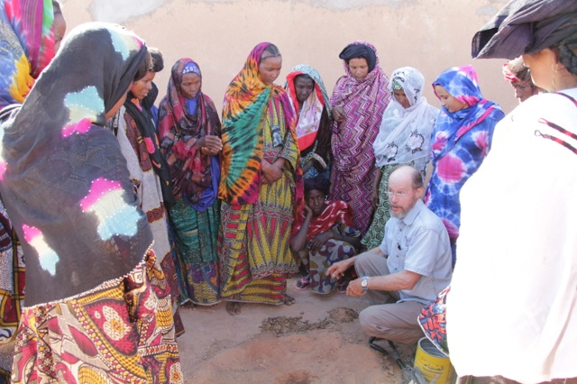 Larry Beckett demonstrates planting moringa seeds with manure and explains their nutritional importance.