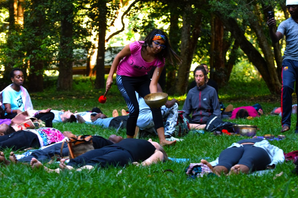 Girl playing a Tibetan singing bowl with friends sitting and lying in the grass and trees meditating
