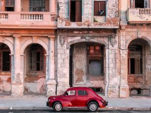 A Well Kept Relic in Front of Crumbling Buildings in Havana