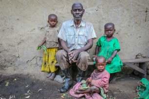 A Banana Gin Distiller with Daughters, Kasenda Crater Lakes, Uganda