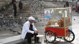 Man selling pastries from cart, on steps of Mosque
