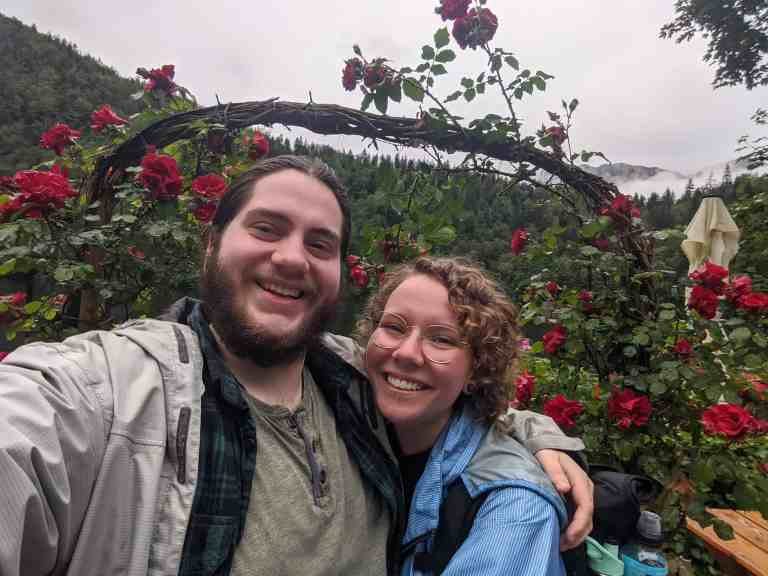 Jenson and Lisa wearing raincoats in front of an arch of roses at fischerhutte on the lake of Toplitz See in the mountains of upper Austria. Taken while travelling around Hallstatt. Mountains or visible in the background.