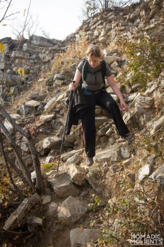 A hiker cautiously descends the rubble that was once the Great Wall of China.