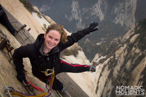 A hiker on the Huashan plank walk dangles her leg over the edge.