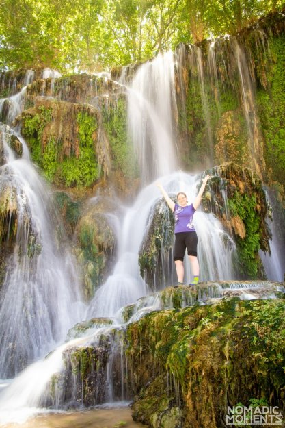 A visitor stands in the waterfall of Fifty Foot Falls.