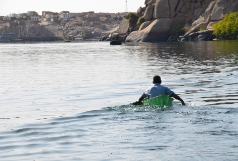 A man paddling away from the island at Philae Temple on Agilkia Island, Egypt