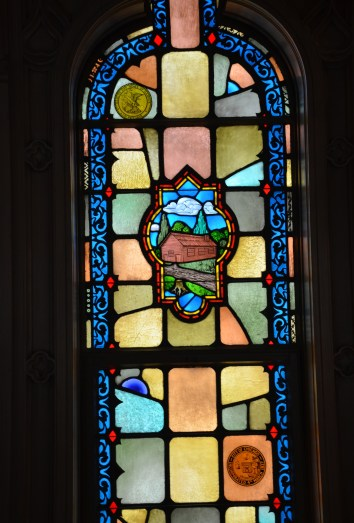 Stained glass window depicting the first log cabin church on the Chicago River in the Chapel in the Sky at the Chicago Temple