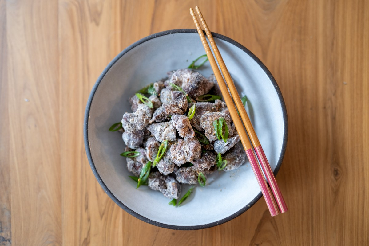 Sous Vide Chicken Gizzard with green scallions in a white bowl and chopsticks on the side