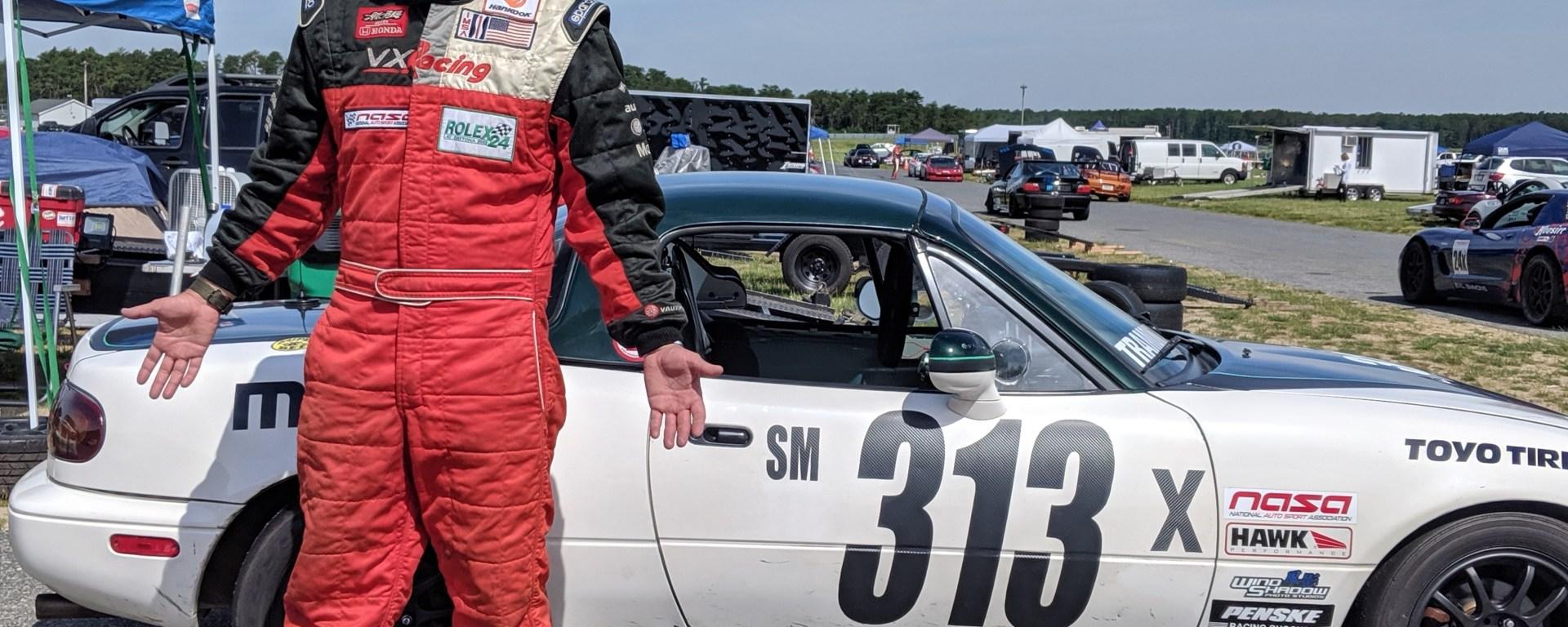 Race Driver in firesuit standing before Spec Miata Racecar