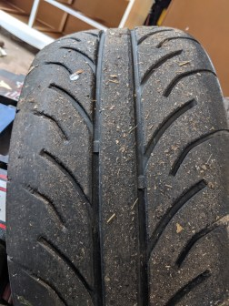 Tire with uneven wear on tread pattern from camber with excessive toe