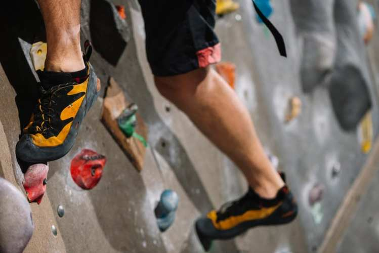 Person's legs on a climbing wall
