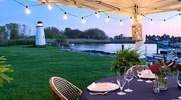 Outdoor dining with view of river and lighthouse.