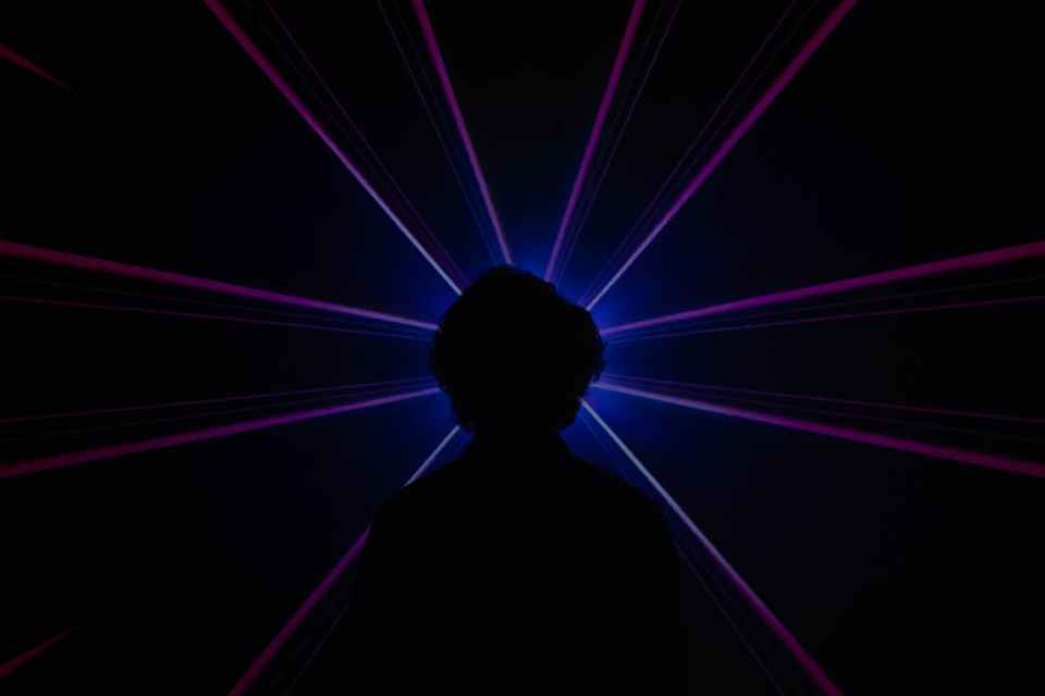silhouette of man standing in front of purple light