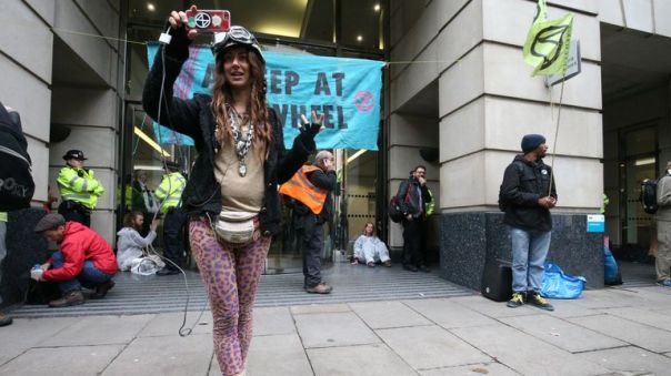 A protester does a live vlog at the Department for Transport amid an Extinction Rebellion (XR) protest outside the building in Horseferry Road, Westminster, London.