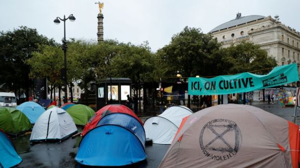 """This picture taken on October 8, 2019, shows tents and a sign reading """"Here we harvest"""" during a demonstration called by climate change activist group Extinction Rebellion, on the Pont au Change bridge in Paris. - Climate protesters from Sydney to London blocked roads starting on October 7, sparking mass arrests at the start of two weeks of civil disobedience demanding immediate action to save the Earth from """"extinction"""". The year-old group Extinction Rebellion has energised a global movement demanding governments drastically cut the carbon emissions that scientists have shown to cause devastating climate change. (Photo by Thomas SAMSON / AFP) (Photo by THOMAS SAMSON/AFP via Getty Images)"""
