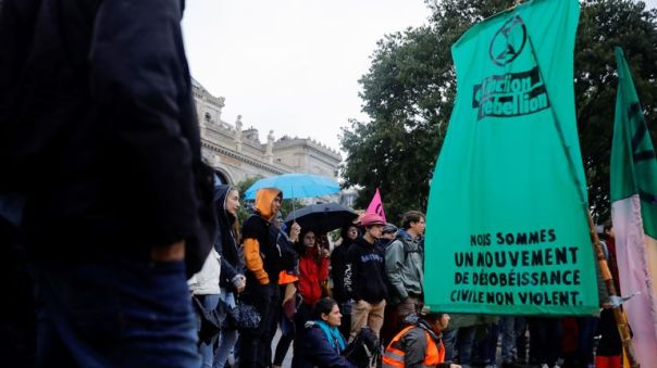 """People hold a """"general assembly"""" next to a flag with the logo of Extinction Rebellion reading """"We are a non-violent civil disobedience movement"""" during a demonstration called by climate change activist group Extinction Rebellion, on October 8, 2019, on the Pont au Change bridge in Paris. - Climate protesters from Sydney to London blocked roads starting on October 7, sparking mass arrests at the start of two weeks of civil disobedience demanding immediate action to save the Earth from """"extinction"""". The year-old group Extinction Rebellion has energised a global movement demanding governments drastically cut the carbon emissions that scientists have shown to cause devastating climate change. (Photo by Thomas SAMSON / AFP) (Photo by THOMAS SAMSON/AFP via Getty Images)"""