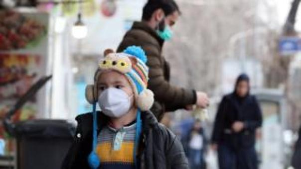 A child wearing a face mask walks on a street in Tehran on 26 February 2020