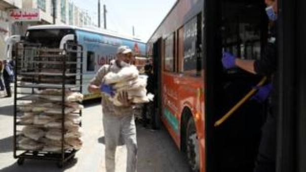 Bakers load bread onto buses for distribution in Jordan's capital, Amman