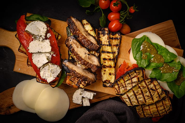 preparation of paninis, layers of grilled vegetables, cheese, spinach, and basil dressing